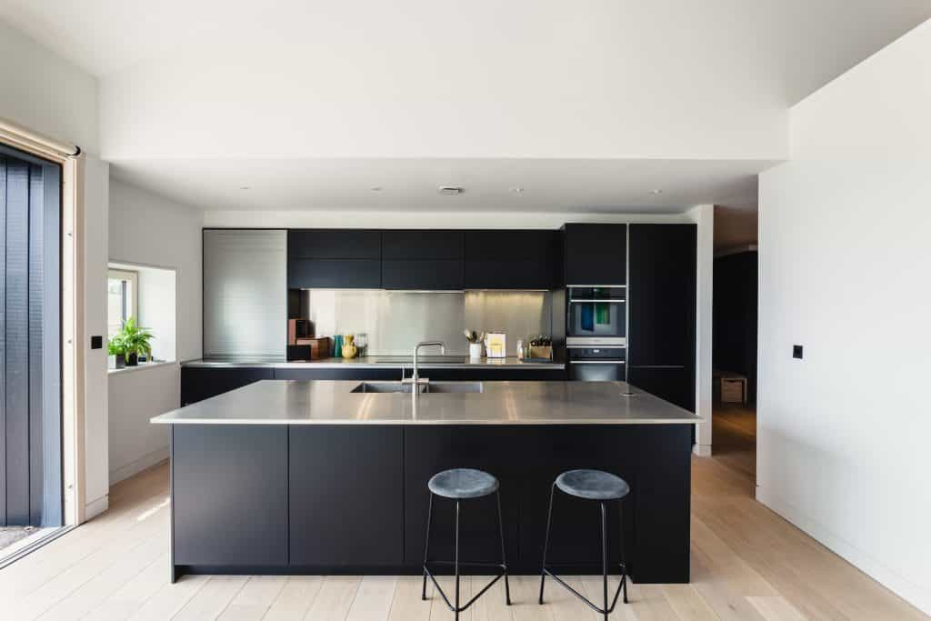 Passive house or passivhaus barn conversion view into modern dark blue kitchen with stainless steel worktops