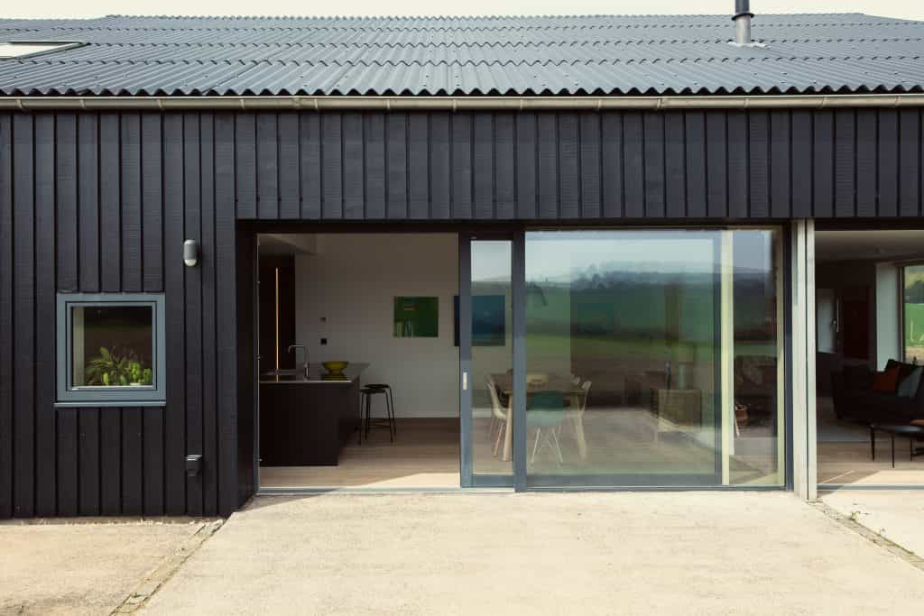 Passive house or passivhaus barn conversion with blackened timber cladding with view into modern kitchen through large glass sliding doors