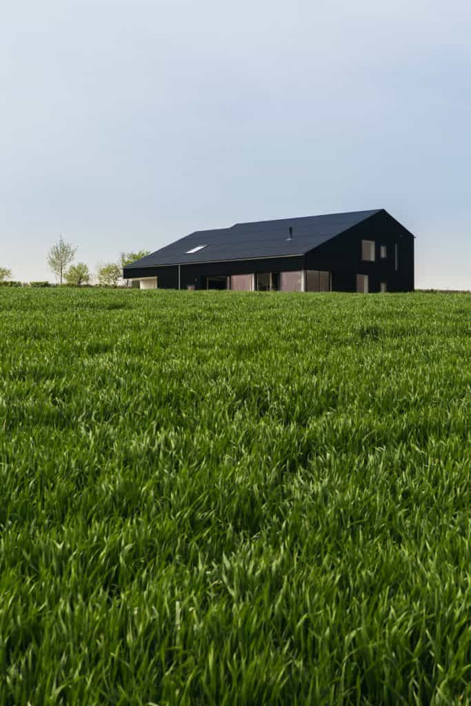 Passive house or passivhaus barn conversion set in green countryside with blackened timber cladding