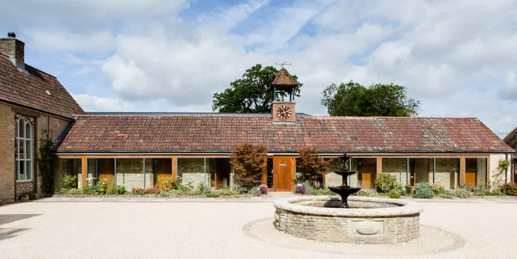 listed building conversion to hotel with cotswold stone and central round water fountain and oak doors and windows