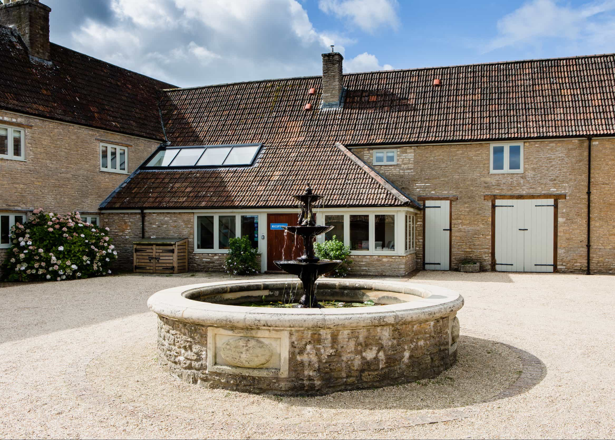 listed building conversion to hotel with cotswold stone and central round water fountain and rose bush with stable doors