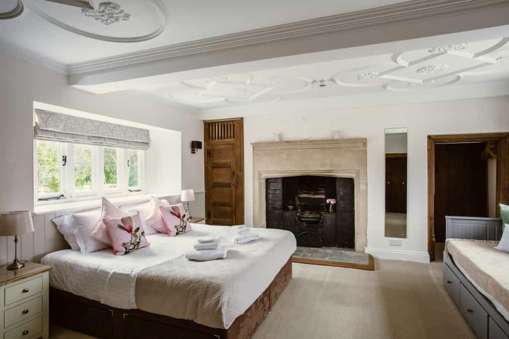 Luxury hotel bedroom with open fireplace and traditional cornicing and ceiling roses with pink pillows