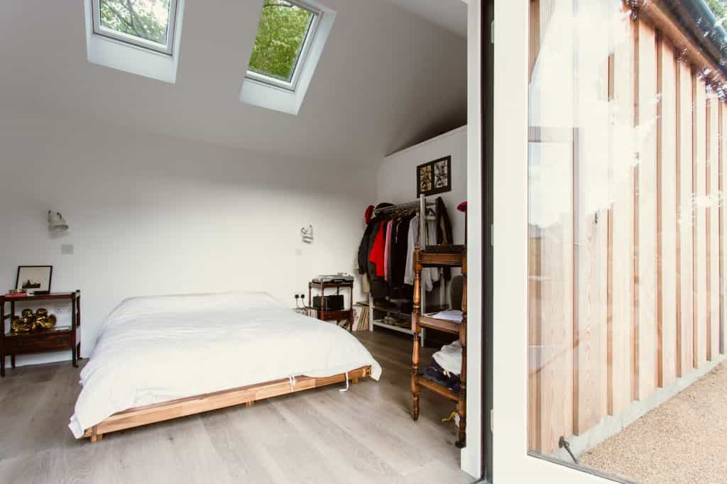 view through double glass patio doors into bedroom lodge with double bed and skylights with external timber cladding