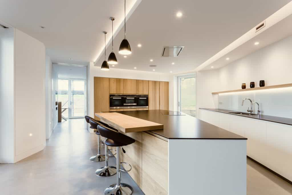 luxury passive house or passivhaus with large kitchen dining space and bar stools with glass doors and black kitchen worktops