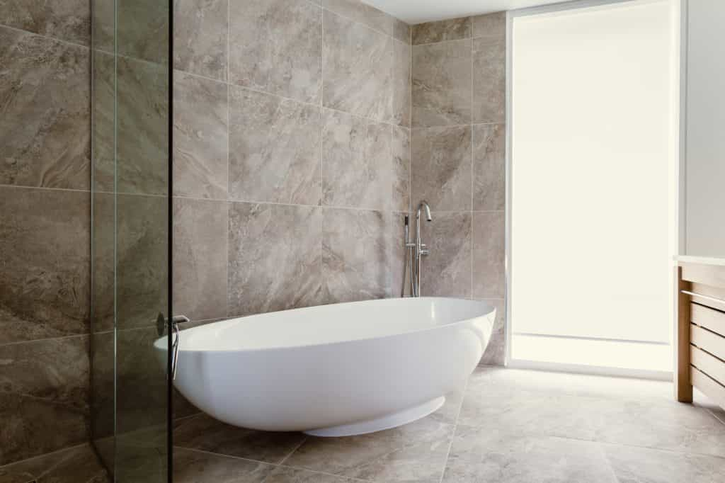 beige marble wall and floor tiles with large white freestanding bath in bathroom