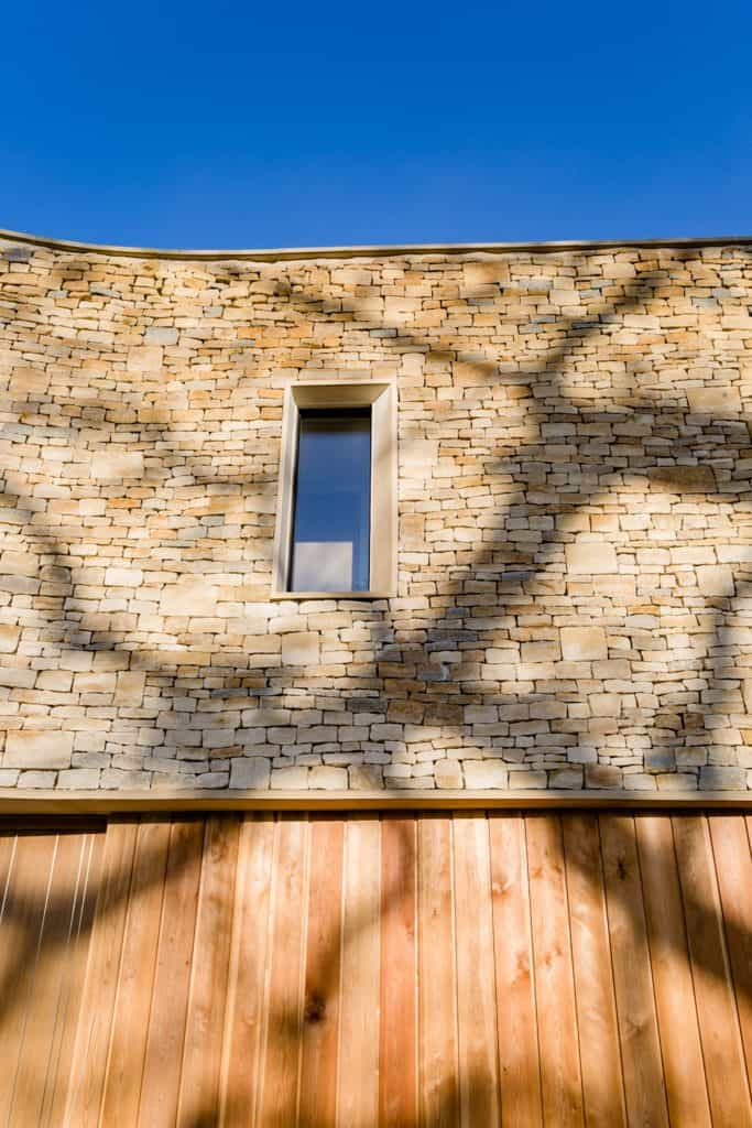 Passive house or passivhaus residence with cotswold stone and timber cladding in the sunshine