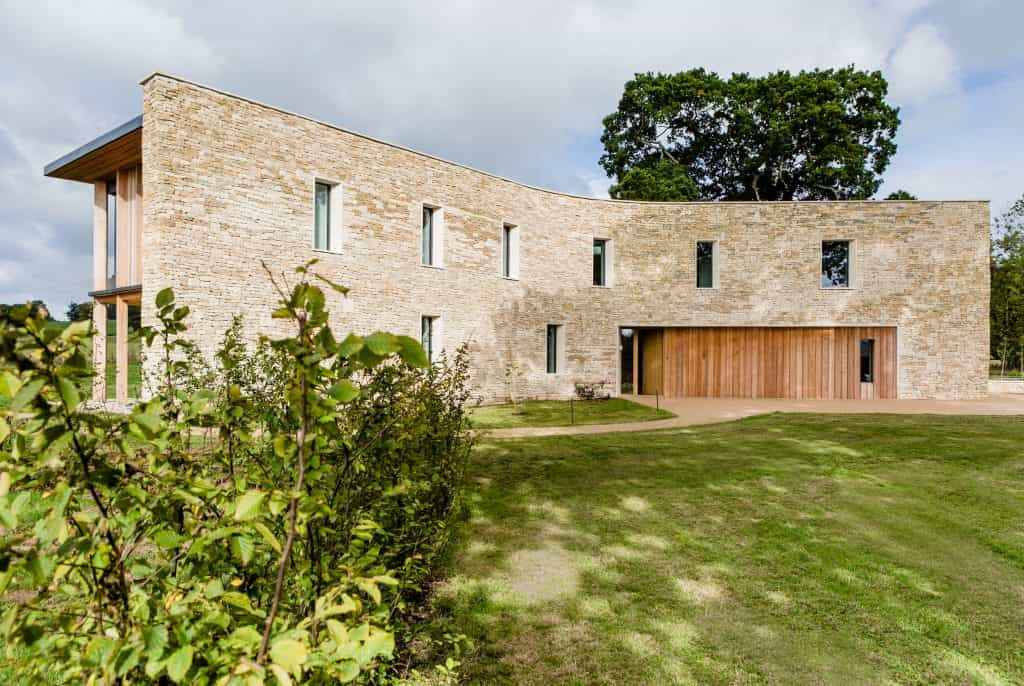 Passive house or passivhaus residence with cotswold stone and timber cladding overlooking meadow and woodland from large glass windows with large bush bottom left