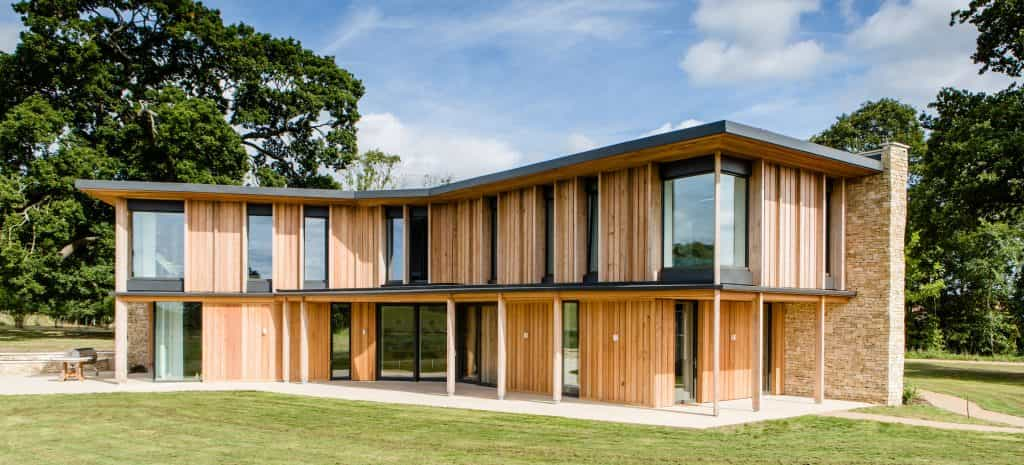 Passive house or passivhaus residence with cotswold stone and timber cladding overlooking meadow and woodland from large glass windows