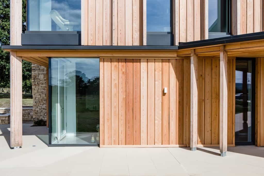 Passive house or passivhaus residence with cotswold stone and timber cladding and large glass windows