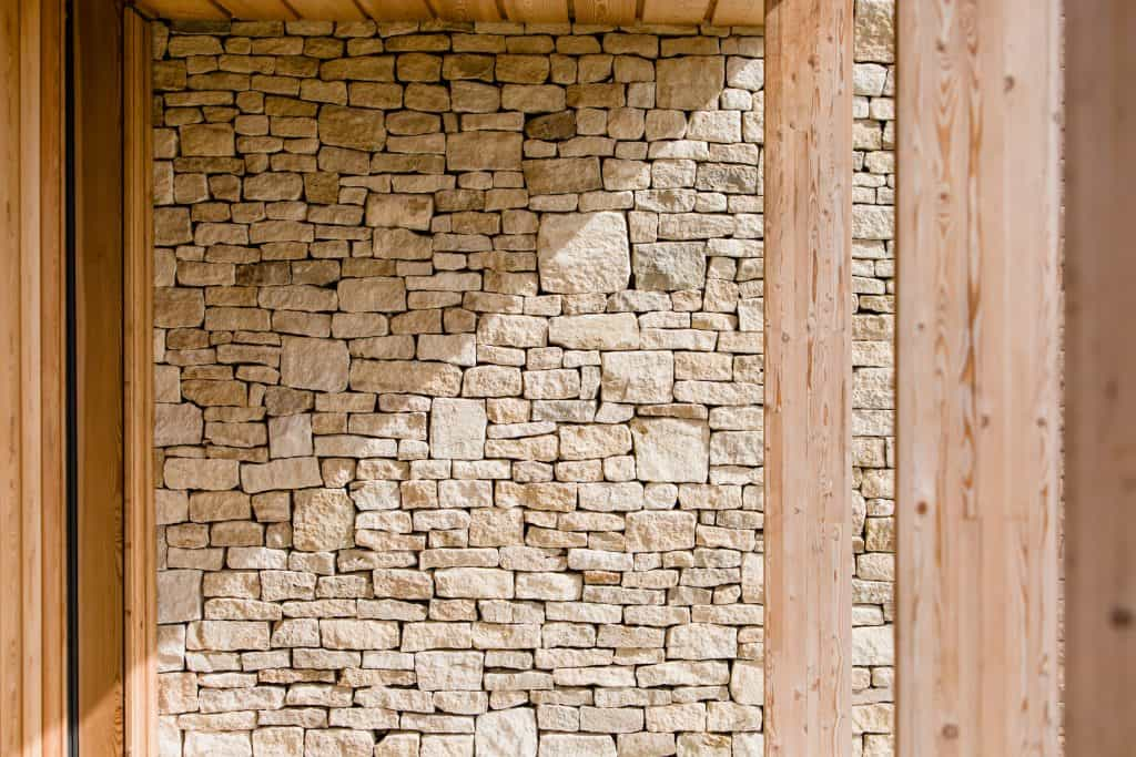 Passive house or passivhaus residence with cotswold stone and timber cladding