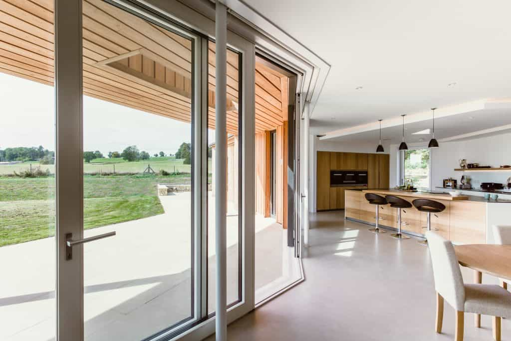 Luxury kitchen with bar stools and pendant lights overlooking large glass sliding doors into garden