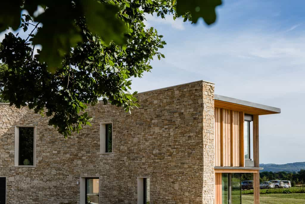 passive house or passivehaus with cotswold stone and timber cladding set in meadow with bush over top right