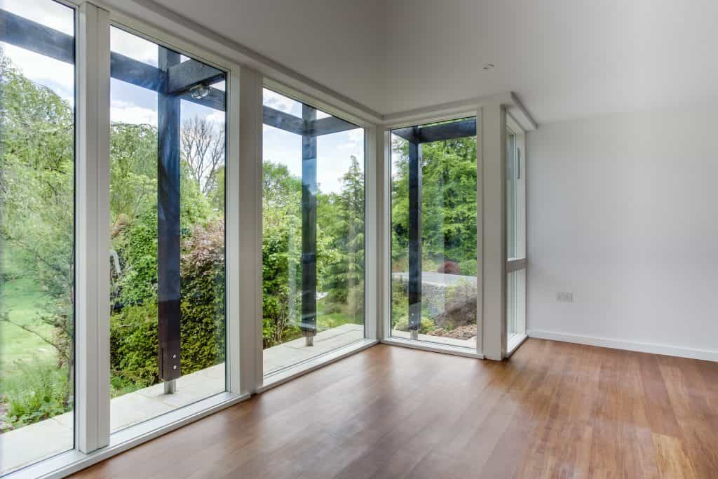 restoration home with timber floor and large glass windows overlooking woodland