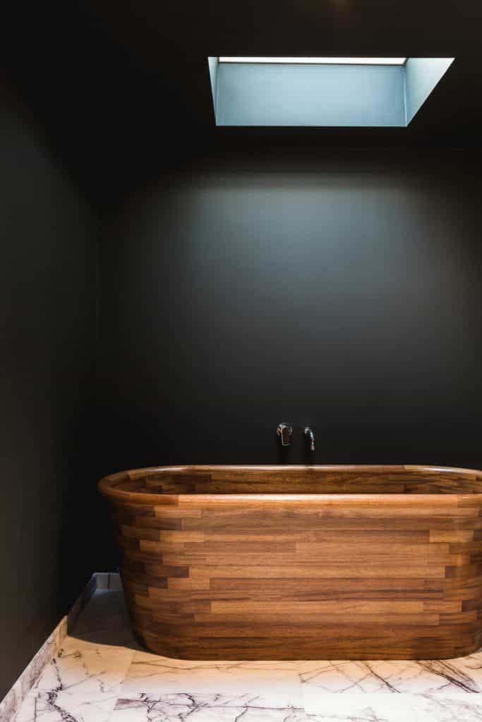 Luxury bathroom with black walls, skylight and bespoke wooden bathtub on white marble floor with black vein