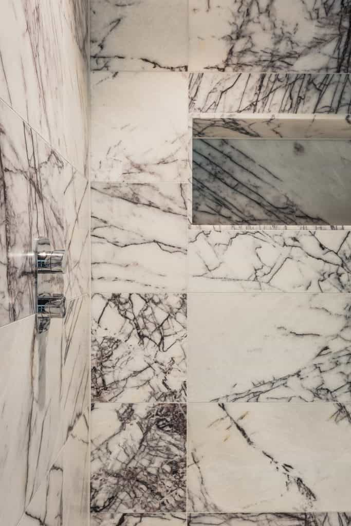 Luxury marble shower with white grout and black marble vein