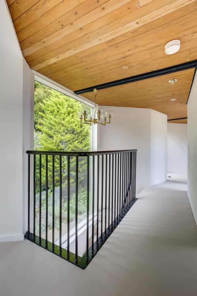 Luxury restoration with timber cladding ceiling and stairs with black iron balustrade