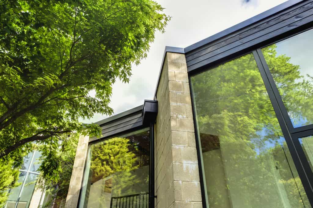 large restoration residence made from Douglas fir pine and Bath stone with large glass windows set within large plot of land in the countryside