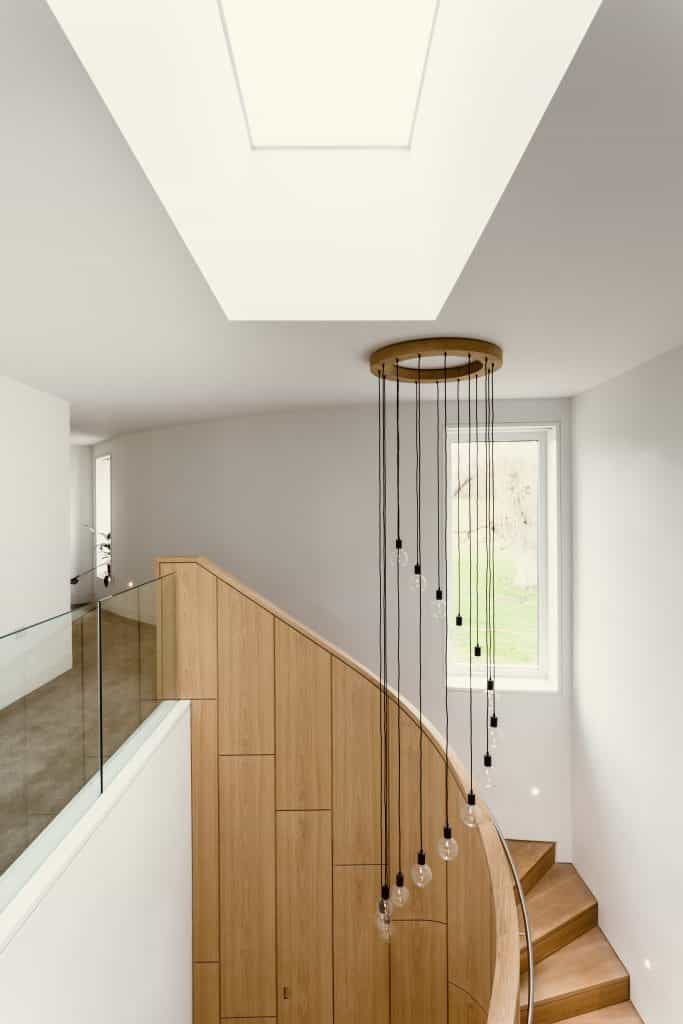 architecturally designed oak staircase with lighting feature and double height ceiling and glass balustrade