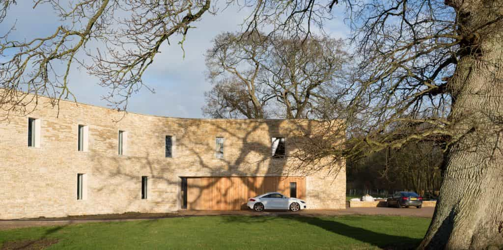 luxury Passivhaus and passive house with Cotswold Stone clad exterior with timber cladding and white Audi TT