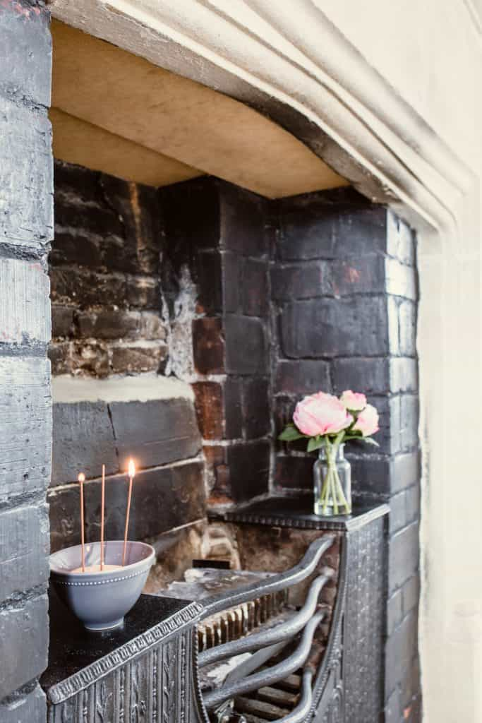 Stone and iron traditional fireplace with flowers and incense