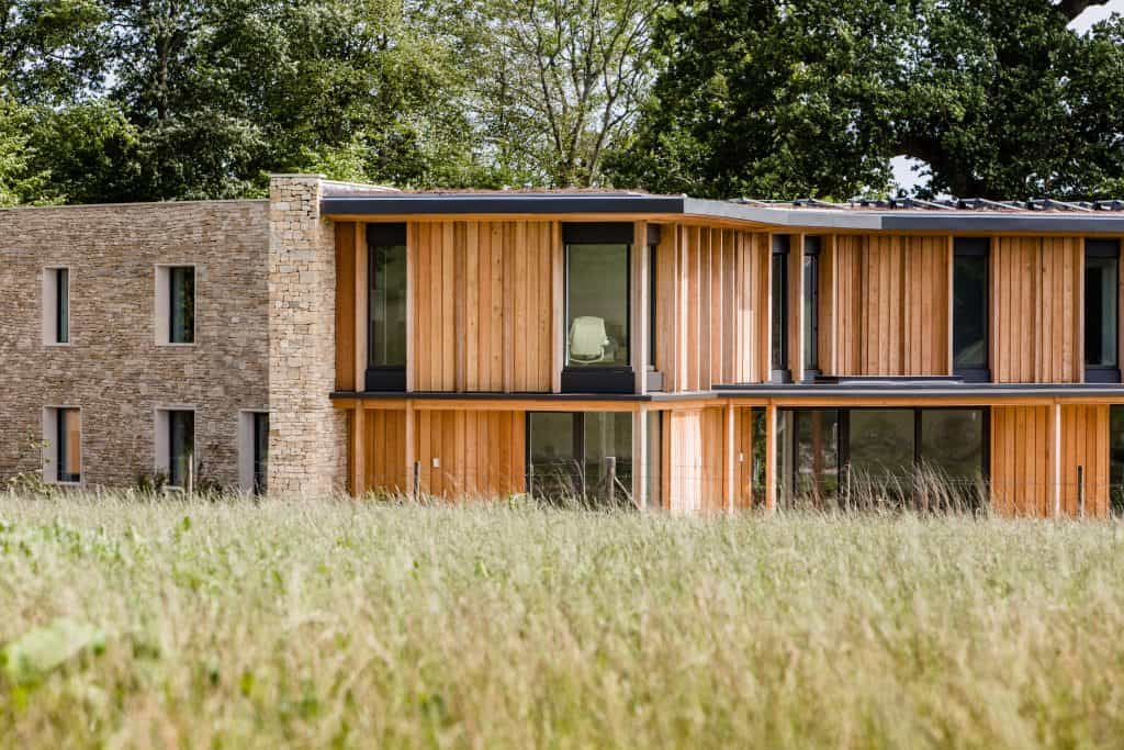 stone and wooden cladding on exterior of passivhaus and passive house building set in greenery