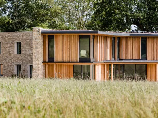 Coswold stone and timber wooden cladding on exterior of passivhaus and passive house building set in greenery