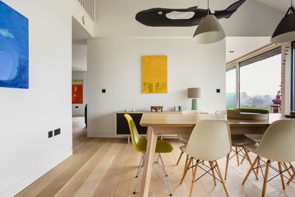 Luxury barn conversion passive house with Architecturally designed dining room with splashes of colour, chairs, tables, art and lighting