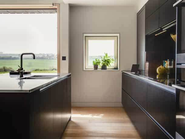 passive house barn conversation with Dark blue bespoke joinery kitchen and bifold doors overlooking the countryside