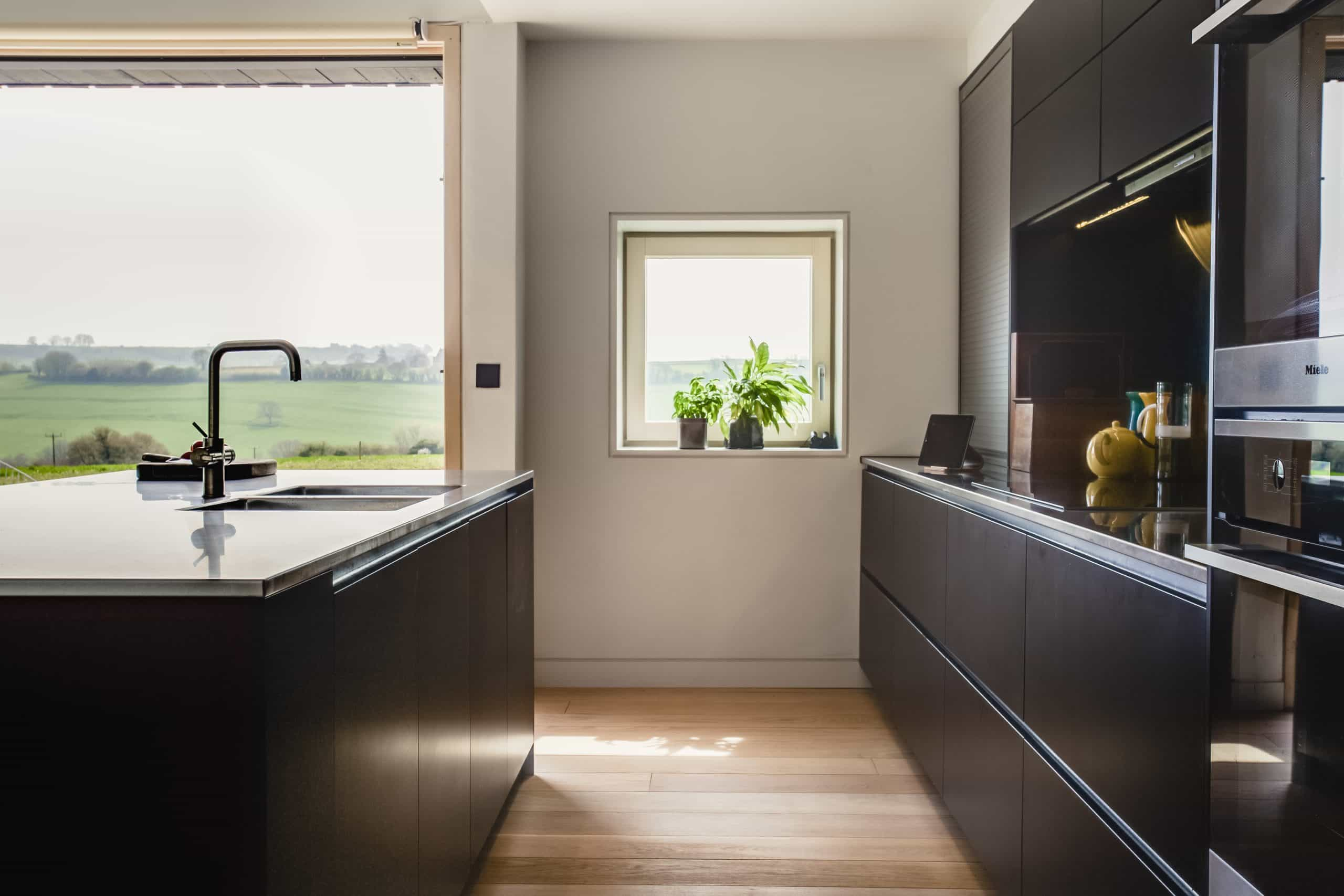 Dark bespoke joinery kitchen with bifold doors overlooking the countryside