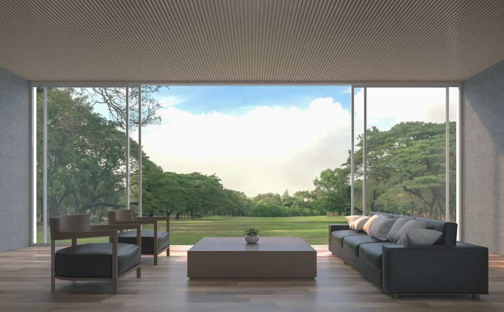 View through property into garden with trees through bi fold glass doors with indoor seating area
