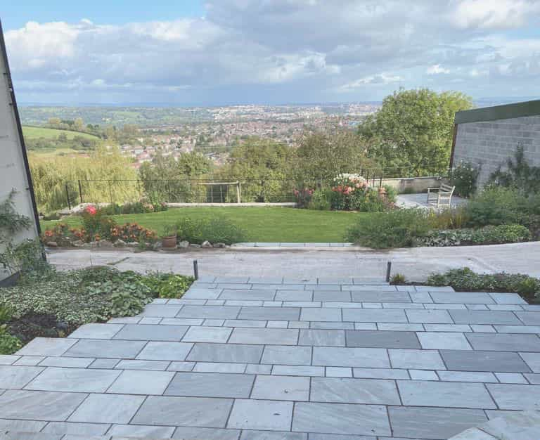 outdoor landscaping with stone terracing and paving in garden with view over city