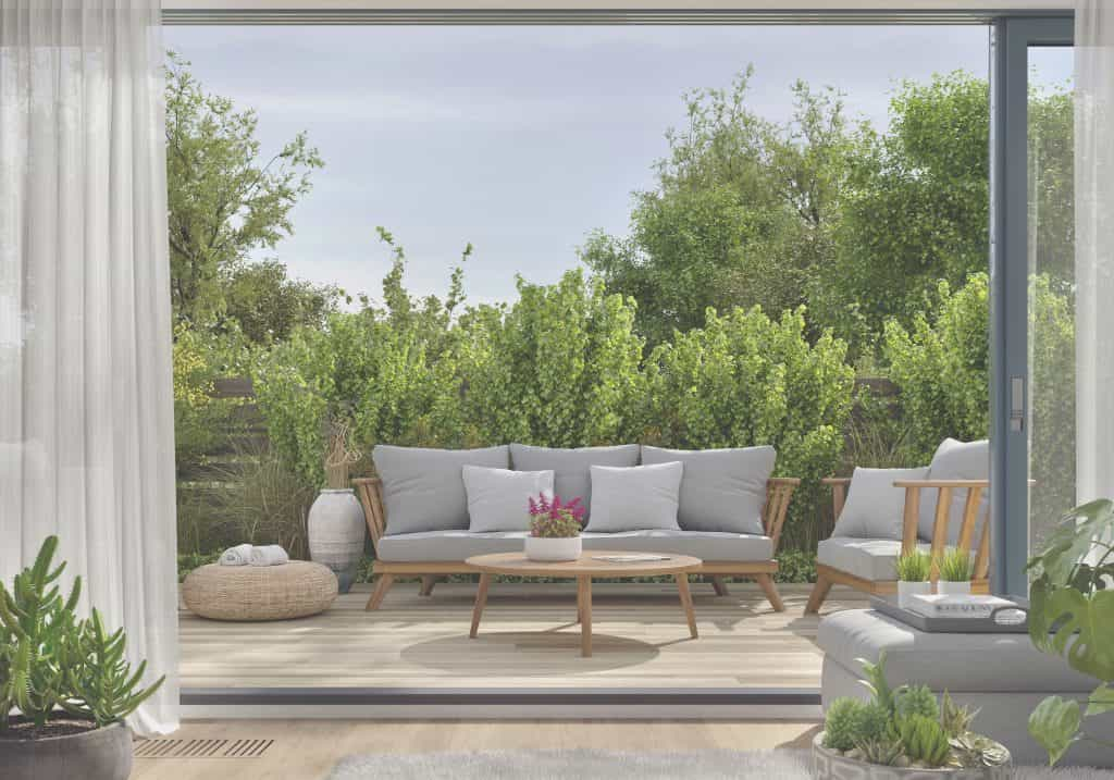 View from property through bi fold doors into seating area in garden with flowers, plants and bushes