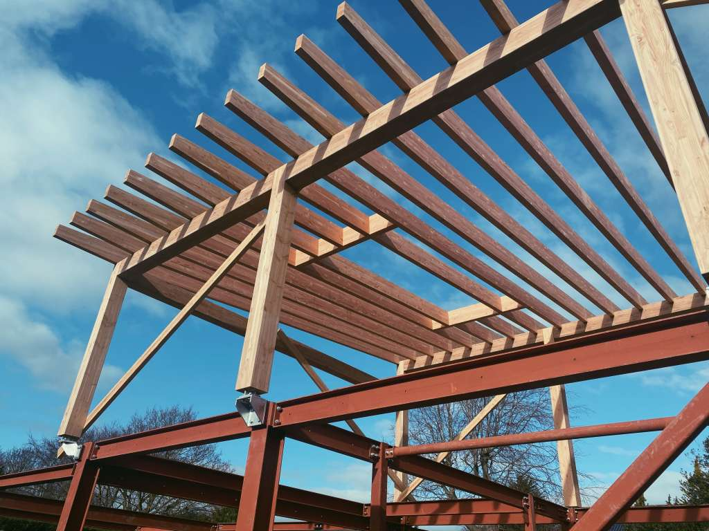 Exposed timber beans with steel frame of passive house with sun shining
