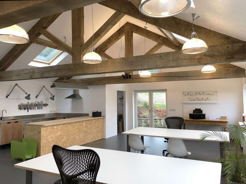 Converted barn with exposed beams with pendant lighting and kitchen