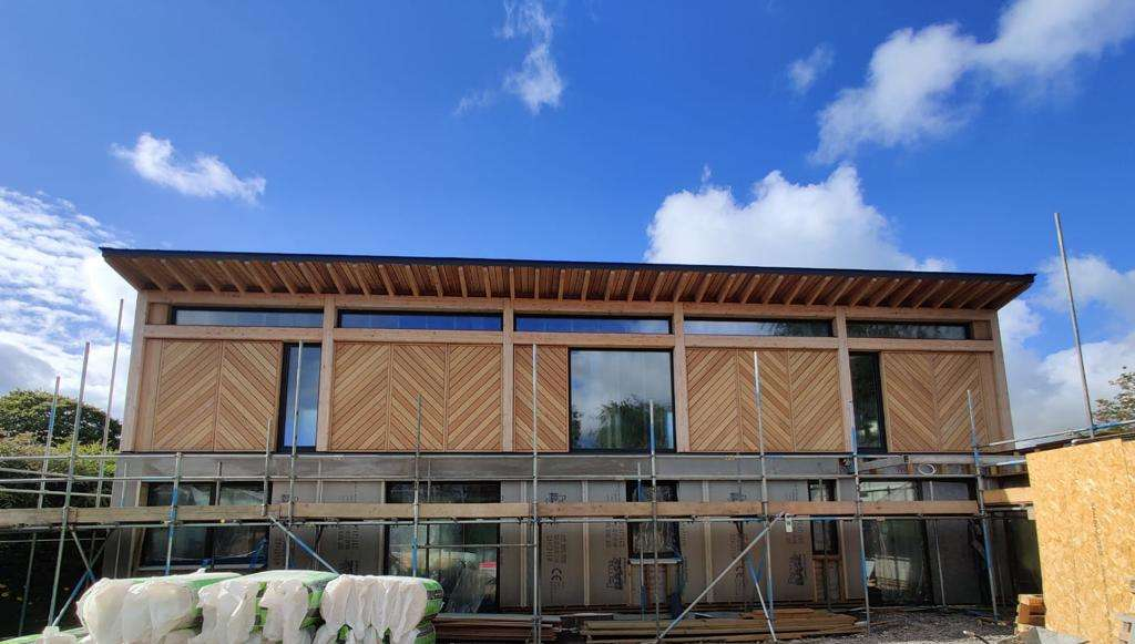 construction of Passive House with timber cladding and scaffolding with large glass windows in the sunshine