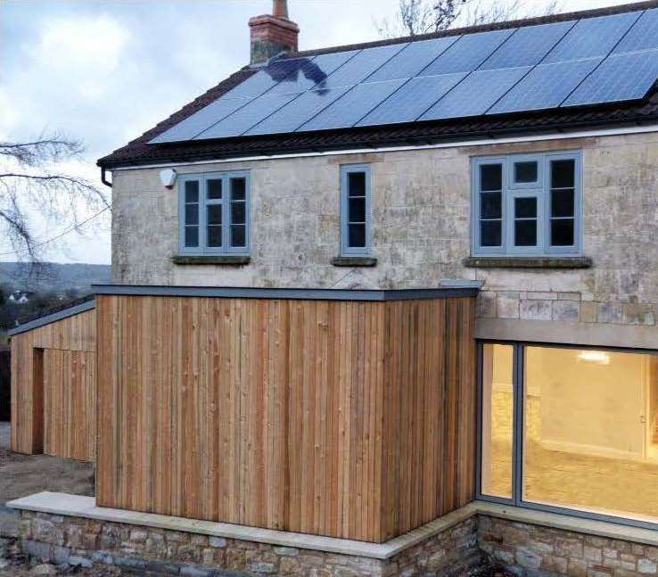 Restored heritage home with timber cladding and dark grey windows at dusk