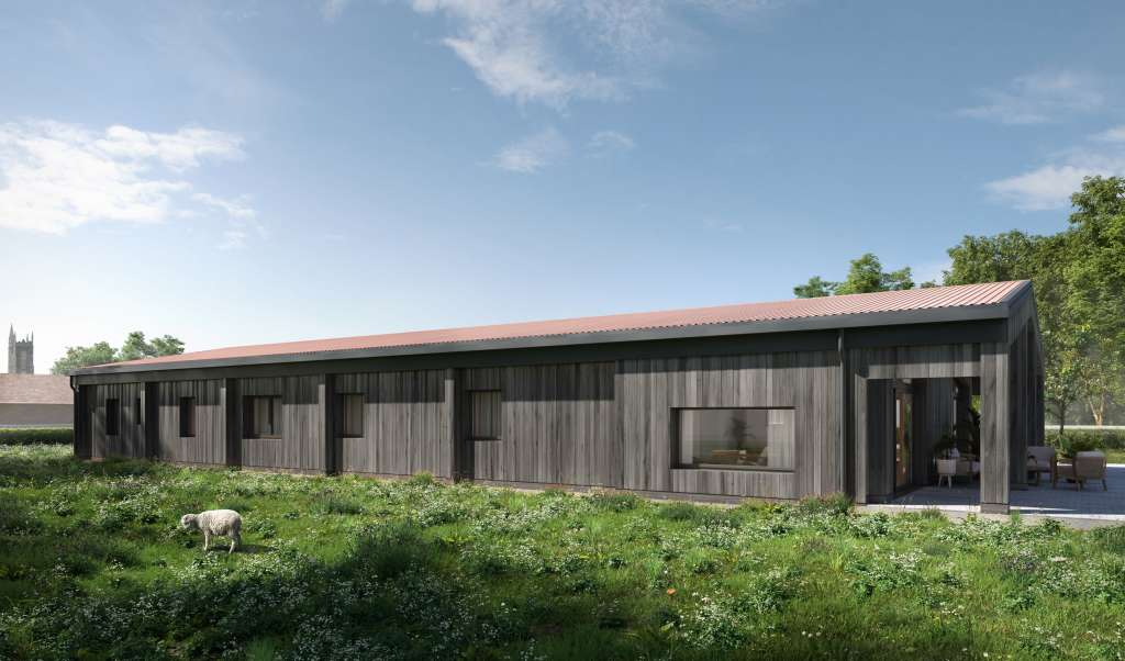 Passive House barn conversion with timber cladding, red roof tiles and a sheep in meadow
