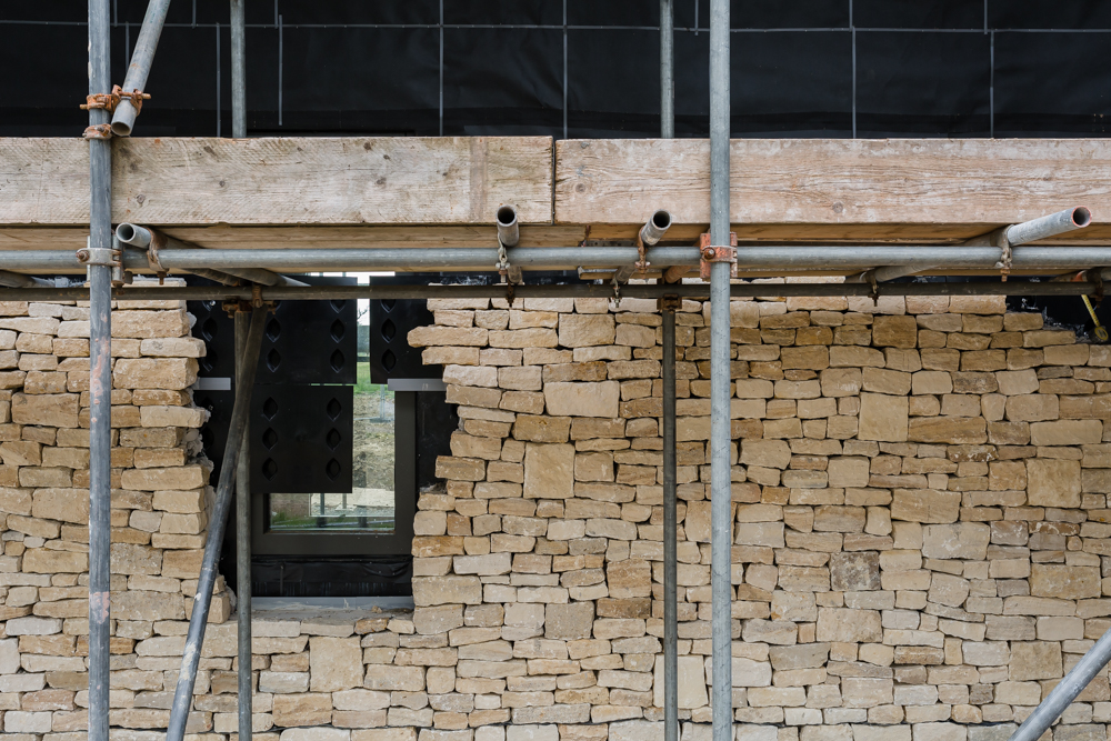 Passive House cotswold stone cladding with scaffolding